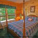 This bedroom is so alluring with its four poster bed in cabin 80 (Heavenly Haven), in Pigeon Forge, Tennessee.