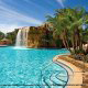Outdoor pool view with a waterfall at the Mystic Dunes Resort in Orlando, Florida.